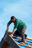 Worker on roof. A workman working on top of a roof without a safety harness royalty free stock photos