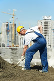 Worker roofer with shovel. Manual worker with shovel at roof construction works in building area Royalty Free Stock Image