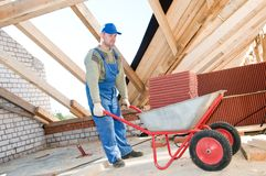 Worker roofer and wheel barrow stock image