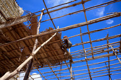 Worker is roofing with leaves. Wooden structure house with blue sky. In India Stock Photo