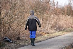 A worker in rubber boots and a jacket walks along an asphalt road past the brushwood in the springtime. Formation of green spaces stock photography