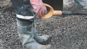 Worker in rubber boots shovel rake brakestone in sewer ditch at building site stock footage