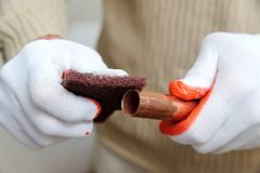 A worker is rubbing the copper tube. Stock Image