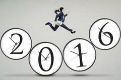 Worker runs on clock with numbers 2016 Stock Photography