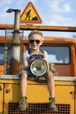 The worker`s boy sits on a yellow, large excavator. royalty free stock photos