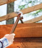 Worker's Hand Hammering Nail On Timber Frame At Royalty Free Stock Images