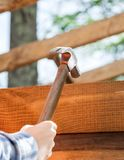 Worker's Hand Hammering Nail On Timber Frame Royalty Free Stock Image