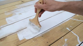 Worker`s hand holding brush and painting white on wood terrace, natural wood floor or wall texture surface. stock video