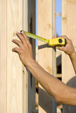 Worker's Hand Measuring Wooden Elements Of House Construction Stock Image