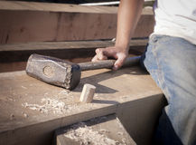Worker's Hand and Sledgehammer Restng on a Timberframe Joint. Timber frame carpenter resting on a large post and beam joint with his sledgehammer and a newly Royalty Free Stock Photos