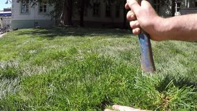 Worker's hand strikes with an ax on the grass for a new lawn slow motion. Close-up worker's hand strikes with an ax on the grass for a new lawn slow motion stock video