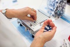 Worker's hands handling pills Stock Photos