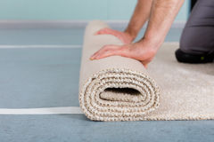 Worker`s Hands Rolling Carpet stock photo