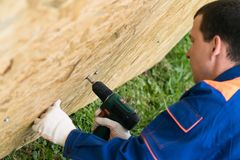 Worker`s hands screwed a wooden shield with a screwdriver, close-up top view stock image