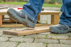 Worker with safety boots steps on a rusty nail Stock Photography