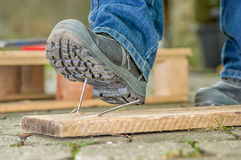 A worker with safety boots steps on a rusty nail Royalty Free Stock Images