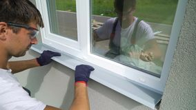 Worker in safety glasses and protective gloves installing metal sill on external PVC window frame. Man worker in safety glasses and protective gloves installing stock footage