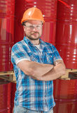 Worker safety helmet standig in front of metal. Worker in safety helmet standig in front of metal barrels Stock Photo