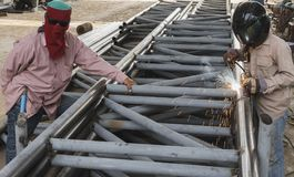 Worker without safety protective welding steel structure. Royalty Free Stock Photos