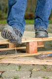 Worker with safety shoes steps on a rusty nail royalty free stock photo