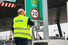 Worker in safety vest changing a sign at a turnpike toll gat royalty free stock photography