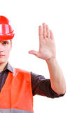Worker in safety vest hard hat showing stop hand. Part of young man construction worker builder foreman in orange safety vest and red hard hat showing stop sign Royalty Free Stock Photography