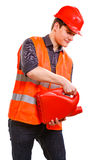 Worker in safety vest with oil fuel. Job and work concept. Young handsome worker wearing orange uniform safety vest with oil gas fuel. Repairman inspector Stock Photography