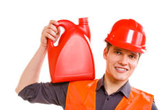 Worker in safety vest with oil fuel. Job and work concept. Young handsome worker wearing orange uniform safety vest with oil gas fuel. Repairman inspector Royalty Free Stock Photo