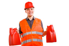 Worker in safety vest with oil fuel. Job and work concept. Young handsome worker wearing orange uniform safety vest with oil gas fuel. Repairman inspector Royalty Free Stock Photos