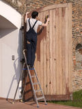 Worker with a sander. Man on a ladder with a sander working on a wooden door removing the varnish stock photography