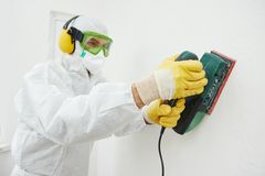 Worker with sander at wall filling. Home improvement worker in protective mask and glasses working with sander for smoothing wall surface Stock Photos