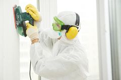 Worker with sander at wall filling. Home improvement worker in protective mask and glasses working with sander for smoothing wall surface Royalty Free Stock Images