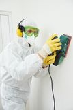 Worker with sander at wall filling. Home improvement worker in protective mask and glasses working with sander for smoothing wall surface Stock Photo