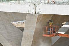 Worker Sanding Under Bridge Stock Photos