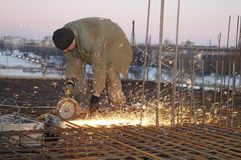 Worker with saw at building. Worker in cutting metal reinforcing lattice with abrasive cutoff saw disk stock photo