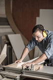 Worker sawing board for furniture. Vertical image of worker sawing board for furniture in carpentry Royalty Free Stock Photos