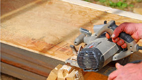 Worker Sawing Wood. Construction sawing wood at construction site Stock Images