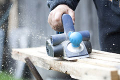 Worker sawing wood board in the workshop. Worker's arm sawing wood board in the workshop Royalty Free Stock Photos