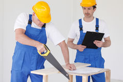 Worker sawing wooden board. Male worker sawing a wooden board at work Stock Photography