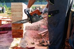 A worker saws off a chainsaw wood Board. House construction. A worker saws off a chainsaw wood Board stock photo