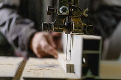The worker saws the workpiece on a jigsaw machine. Front view royalty free stock photos