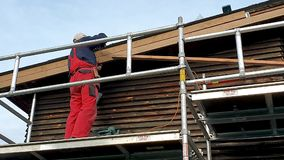 Worker on scaffolding installing new wooden planks on house roof eaves