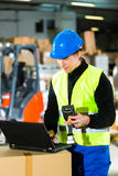 Worker with scanner and laptop at forwarding. Warehouseman with protective vest, scanner and laptop in warehouse at freight forwarding company Stock Photography