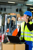 Worker with scanner and laptop at forwarding. Warehouseman with protective vest, scanner and laptop in warehouse at freight forwarding company using a mobile Stock Image