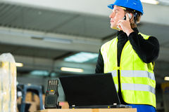 Worker with scanner and laptop at forwarding. Warehouseman with protective vest, scanner and laptop in warehouse at freight forwarding company using a mobile Stock Photos