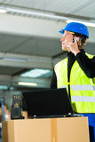 Worker with scanner and laptop at forwarding. Warehouseman with protective vest, scanner and laptop in warehouse at freight forwarding company using a mobile Stock Photography