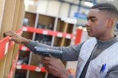 Worker scanning barcode in warehouse Royalty Free Stock Photos