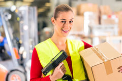 Worker scans package in warehouse of forwarding. Female worker with protective vest and scanner, scans bar-code of package, standing at warehouse of freight royalty free stock images