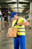 Worker scans package in warehouse of forwarding. Warehouseman with protective vest and scanner, scans bar-code of package, he standing at warehouse of freight Stock Photo