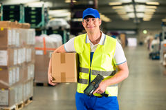 Worker scans package in warehouse of forwarding. Warehouseman with protective vest and scanner, scans bar-code of package, he standing at warehouse of freight Stock Photos